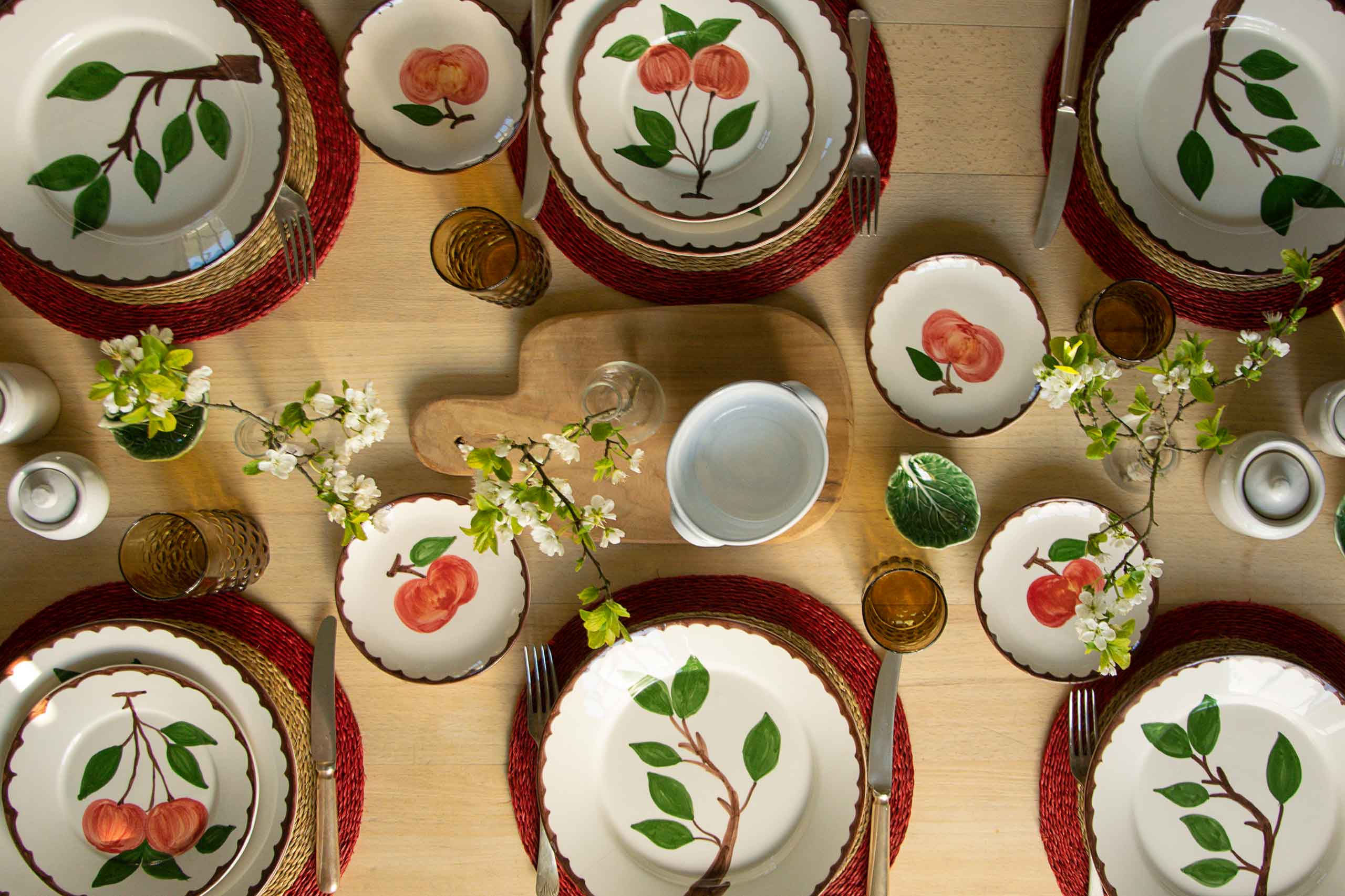 Hand painted plates with apple design on a table set for dinner from Pascale Store